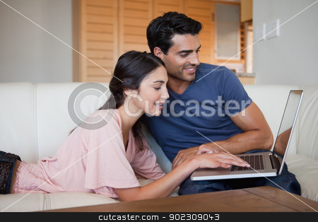 Charming young couple using a laptop stock photo, Charming young couple using a laptop in their living room by Wavebreak Media