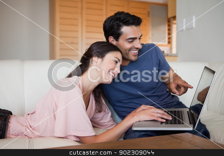 Lovely young couple using a laptop stock photo, Lovely young couple using a laptop in their living room by Wavebreak Media