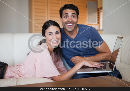 Laughing young couple using a notebook stock photo, Laughing young couple using a notebook in their living room by Wavebreak Media