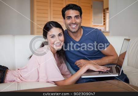 Lovely young couple using a notebook stock photo, Lovely young couple using a notebook in their living room by Wavebreak Media