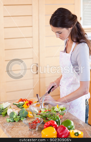 Portrait of a young woman chopping pepper stock photo, Portrait of a young woman chopping pepper in her kitchen by Wavebreak Media