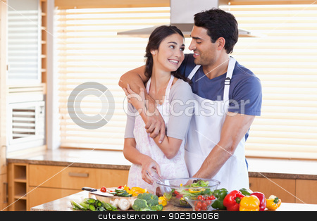 Lovely young couple posing stock photo, Lovely young couple posing in their kitchen by Wavebreak Media