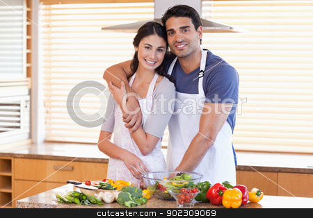 Charming young couple posing stock photo, Charming young couple posing in their kitchen by Wavebreak Media