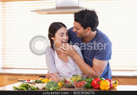 Man feeding his wife stock photo, Man feeding his wife in their kitchen by Wavebreak Media