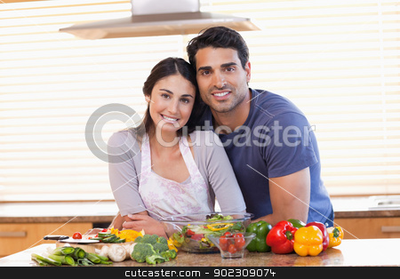 Cute couple looking at the camera stock photo, Cute couple looking at the camera in their kitchen by Wavebreak Media