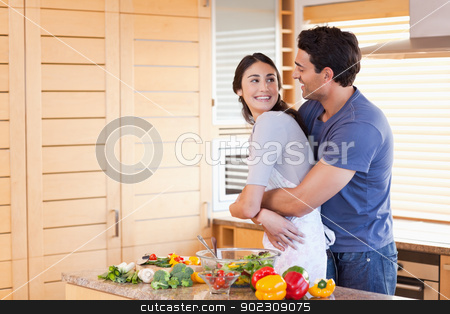 Lovely couple embracing each other stock photo, Lovely couple embracing each other in their kitchen by Wavebreak Media