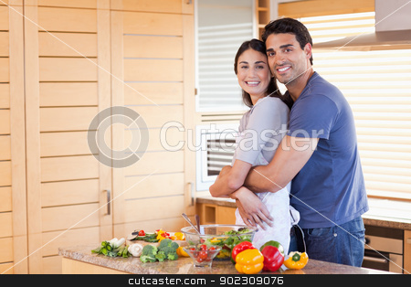 Charming couple embracing each other stock photo, Charming couple embracing each other in their kitchen by Wavebreak Media