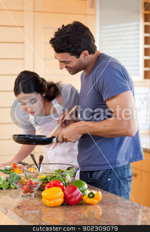 Portrait of a young couple cooking with a pan stock photo, Portrait of a young couple cooking with a pan in their kitchen by Wavebreak Media