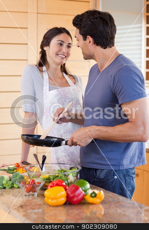 Portrait of a beautiful couple cooking with a pan stock photo, Portrait of a beautiful couple cooking with a pan in their kitchen by Wavebreak Media