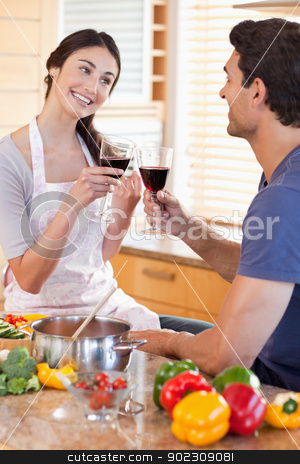 Portrait of a couple having a glass of red wine while cooking stock photo, Portrait of a couple having a glass of red wine while cooking in their kitchen by Wavebreak Media