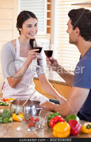 Portrait of a couple having a glass of wine while cooking stock photo, Portrait of a couple having a glass of wine while cooking in their kitchen by Wavebreak Media