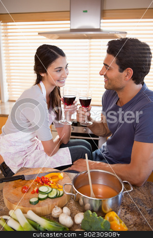 Portrait of a happy couple having a glass of wine while cooking stock photo, Portrait of a happy couple having a glass of wine while cooking in their kitchen by Wavebreak Media