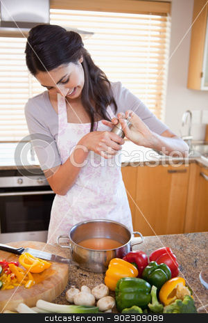 Portrait of a woman preparing a sauce stock photo, Portrait of a woman preparing a sauce in her kitchen by Wavebreak Media