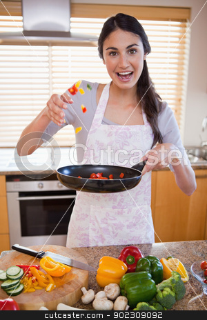 Portrait of a happy woman preparing a dish stock photo, Portrait of a happy woman preparing a dish in her kitchen by Wavebreak Media