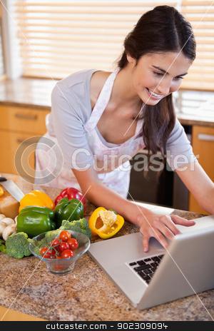 Portrait of a woman looking for a recipe on the internet stock photo, Portrait of a woman looking for a recipe on the internet in her kitchen by Wavebreak Media
