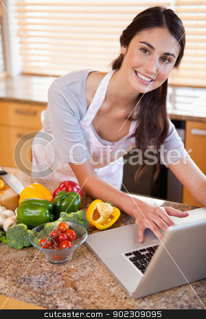 Portrait of a young woman looking for a recipe on the internet stock photo, Portrait of a young woman looking for a recipe on the internet in her kitchen by Wavebreak Media
