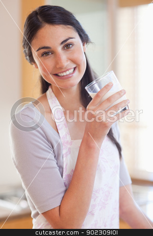 Portrait of a beautiful woman drinking milk stock photo, Portrait of a beautiful woman drinking milk in her kitchen by Wavebreak Media