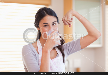 Healthy woman drinking milk stock photo, Healthy woman drinking milk in her kitchen by Wavebreak Media