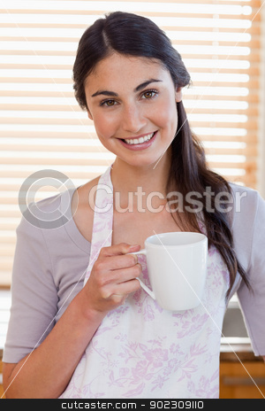Portrait of a woman holding a cup of coffee stock photo, Portrait of a woman holding a cup of coffee in her kitchen by Wavebreak Media
