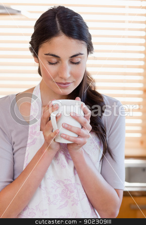 Portrait of a woman smelling a cup of coffee stock photo, Portrait of a woman smelling a cup of coffee in her kitchen by Wavebreak Media