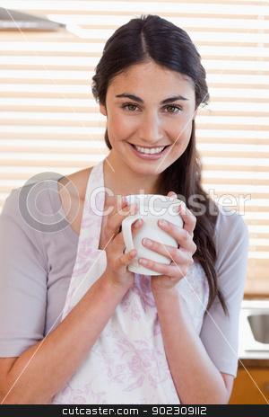Portrait of a woman holding a cup of tea stock photo, Portrait of a woman holding a cup of tea in her kitchen by Wavebreak Media