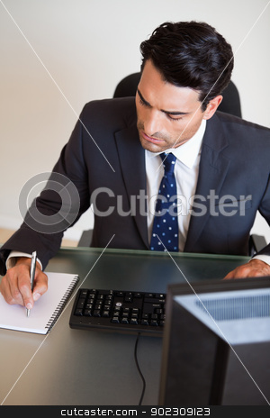 Portrait of a businessman taking notes stock photo, Portrait of a businessman taking notes in his office by Wavebreak Media