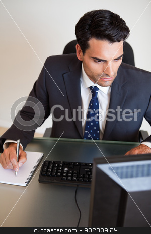 Portrait of a serious businessman taking notes stock photo, Portrait of a serious businessman taking notes in his office by Wavebreak Media