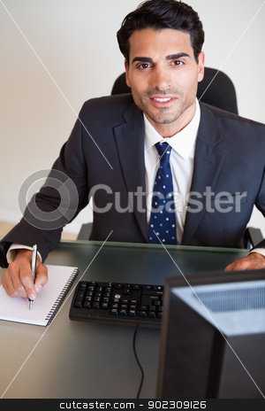 Portrait of a handsome businessman taking notes stock photo, Portrait of a handsome businessman taking notes in his office by Wavebreak Media
