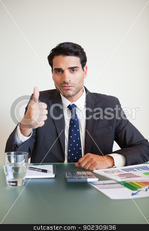 Portrait of a businessman with the thumb up stock photo, Portrait of a businessman with the thumb up in his office by Wavebreak Media
