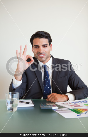 Portrait of a businessman signing everything is perfect stock photo, Portrait of a businessman signing everything is perfect in his office by Wavebreak Media