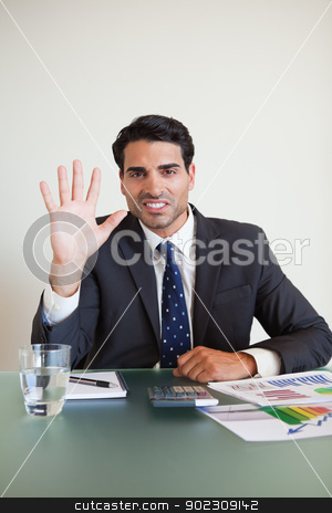 Portrait of a businessman showing his hand stock photo, Portrait of a businessman showing his hand in his office by Wavebreak Media