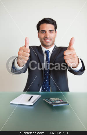 Portrait of a young accountant with the thumbs up stock photo, Portrait of a young accountant with the thumbs up in his office by Wavebreak Media