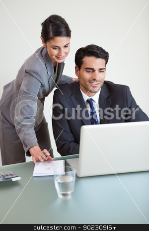 Portrait of sales persons working with a laptop stock photo, Portrait of sales persons working with a laptop in an office by Wavebreak Media