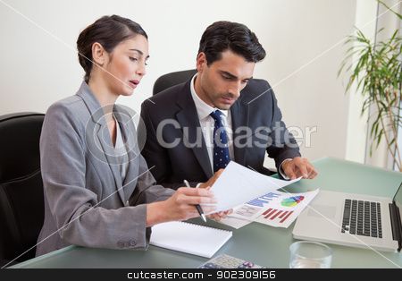 Sales persons working with a notebook stock photo, Sales persons working with a notebook in an office by Wavebreak Media