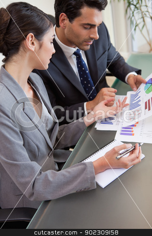 Portrait of sales persons studying graphs stock photo, Portrait of sales persons studying graphs in a meeting room by Wavebreak Media