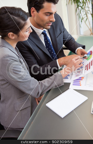 Portrait of young sales persons studying statistics stock photo, Portrait of young sales persons studying statistics in an office by Wavebreak Media
