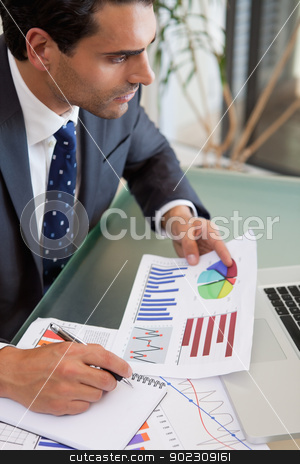 Portrait of a sales person studying statistics stock photo, Portrait of a sales person studying statistics in an office by Wavebreak Media