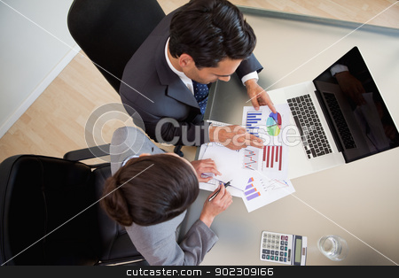 Sales persons studying statistics stock photo, Sales persons studying statistics in an office by Wavebreak Media