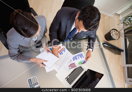 Focused sales persons studying statistics stock photo, Focused sales persons studying statistics in an office by Wavebreak Media