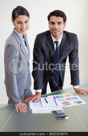 Portrait of smiling sales persons studying their results stock photo, Portrait of smiling sales persons studying their results in an office by Wavebreak Media