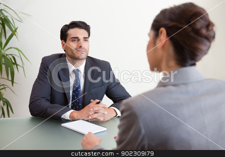 Handsome manager interviewing a female applicant stock photo, Handsome manager interviewing a female applicant in his office by Wavebreak Media