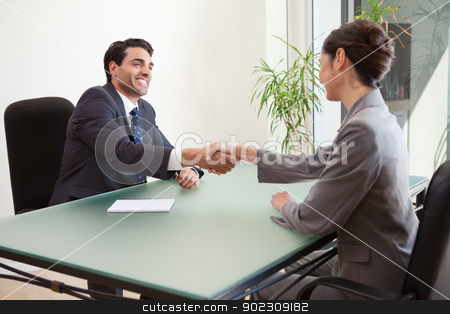 Smiling manager interviewing a good looking applicant stock photo, Smiling manager interviewing a good looking applicant in his office by Wavebreak Media