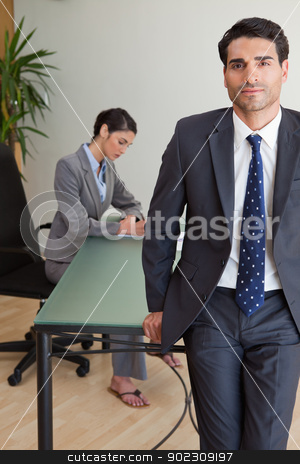 Portrait of a businessman posing while his colleague is working stock photo, Portrait of a businessman posing while his colleague is working in an office by Wavebreak Media