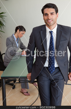 Portrait of a handsome businessman posing while his colleague is stock photo, Portrait of a handsome businessman posing while his colleague is working in an office by Wavebreak Media