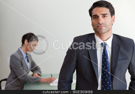 Handsome businessman posing while his colleague is working stock photo, Handsome businessman posing while his colleague is working in an office by Wavebreak Media
