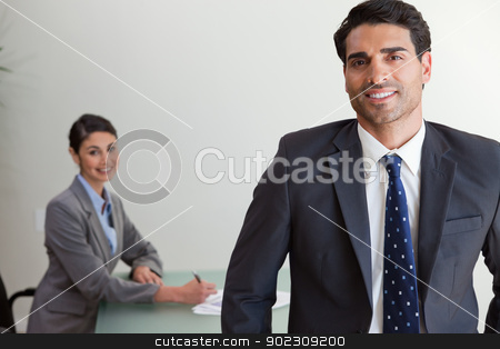 Good looking businessman posing while his colleague is working stock photo, Good looking businessman posing while his colleague is working in an office by Wavebreak Media