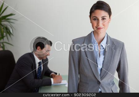 Beautiful businesswoman posing while her colleague is working stock photo, Beautiful businesswoman posing while her colleague is working in an office by Wavebreak Media