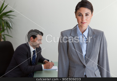 Gorgeous businesswoman posing while her colleague is working stock photo, Gorgeous businesswoman posing while her colleague is working in an office by Wavebreak Media