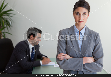 Professional businesswoman posing while her colleague is working stock photo, Professional businesswoman posing while her colleague is working in an office by Wavebreak Media
