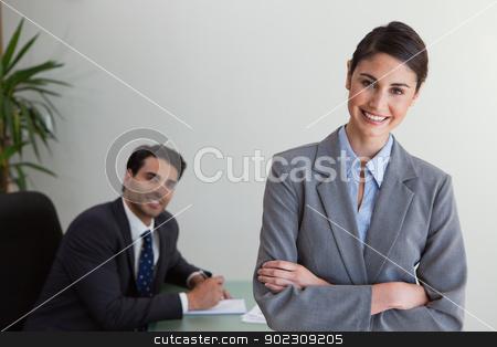 Happy businesswoman posing while her colleague is working stock photo, Happy businesswoman posing while her colleague is working in an office by Wavebreak Media
